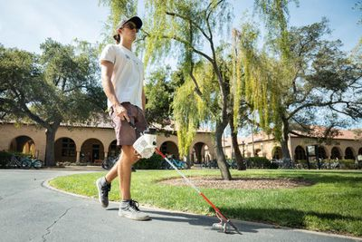 Someone using a robotic cane to help navigate a walkway.