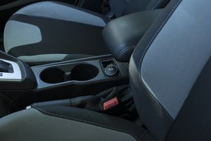 12V socket near a cupholder between two seats.