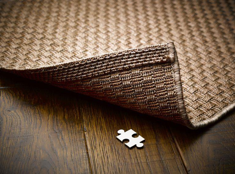A puzzle piece underneath a rug