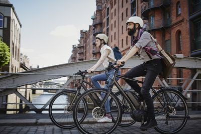 Couple riding electric bicycles in city
