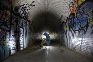 Man surfing on a laptop computer in a pedestrian tunnel, symbolic image for computer hacking, computer crime, cybercrime, data theft