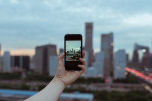 A photo of a hand holding a phone, snapping a shot of a city skyline.