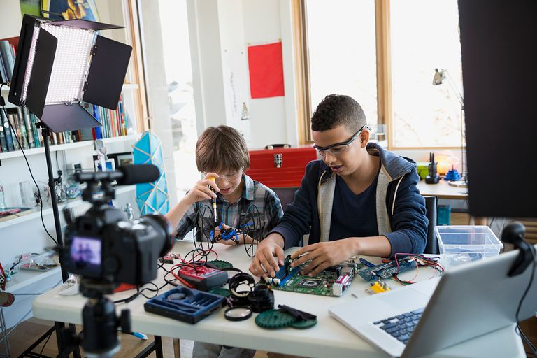 Boys videotaping circuit board assembly in bedroom.