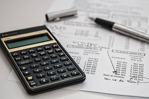 Accounting figures with a calculator and pen sitting on papers.