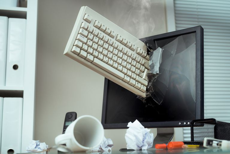 Pnotograph of a keyboard smashed through a computer LCD monitor