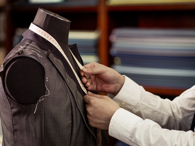 Tailor measuring garment in traditional tailors shop
