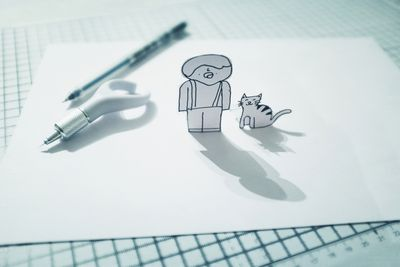 Cat and person paper cutout effect over drawing paper