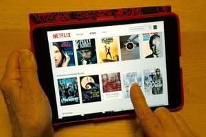 A person navigating Netflix on a tablet