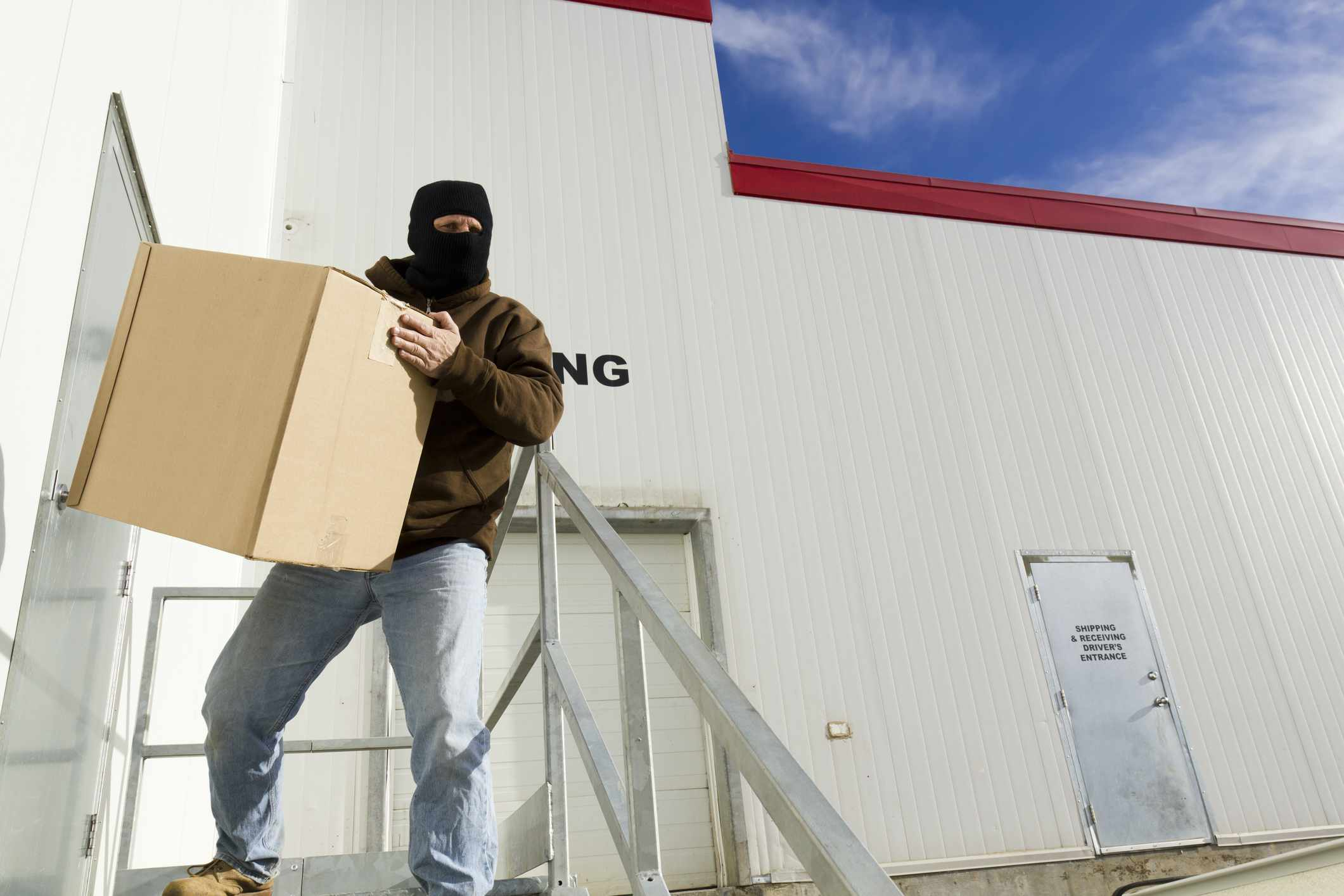 Man wearing a ski mask and stealing a package from a warehouse