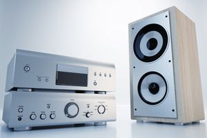 A home stereo receiver and amplifier next to a single bookshelf speaker