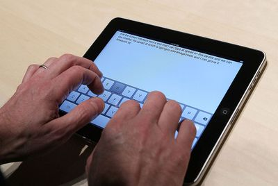 Hands typing on iPad