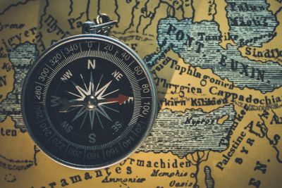 Compass laying on top of a brown map