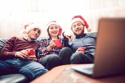 An image of three friends wearing Santa hats while watching a laptop.