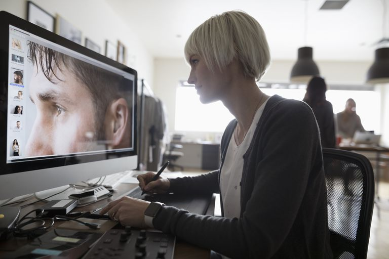 Female photo editor using graphics tablet, editing digital photograph on computer in office