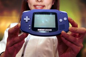 A woman holding a Game Boy Advance.