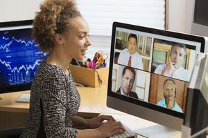A woman sitting at a desk watching a video conference call with 4 other people