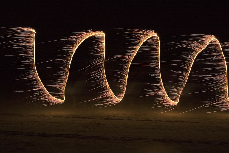Sparklers painting cosine at night on beach