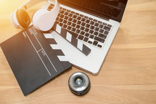 Clapboard, headphones, camera lens, and computer on a desk representing film making and video editing