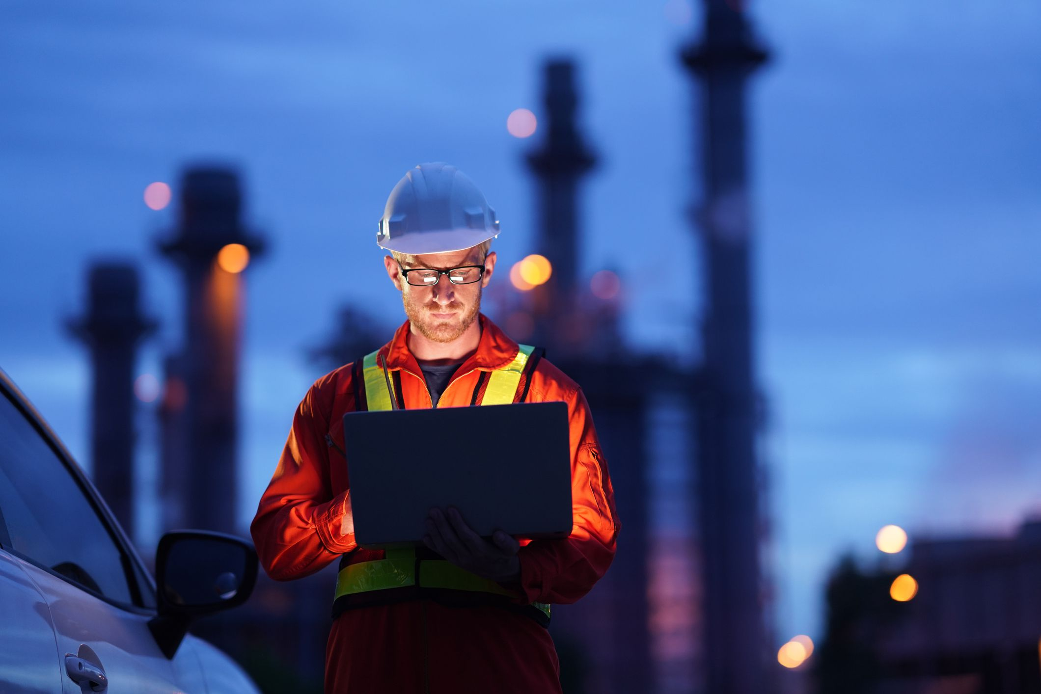 A construction worker using a laptop outside at dusk with a factory in the background.