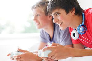 Two teenage boys playing Xbox video games while lying on a bed