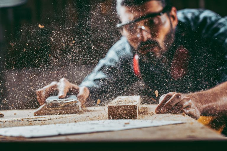 A carpenter sanding his work