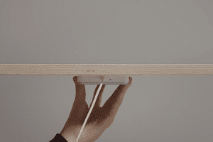Ikea's new wireless charger connected to the bottom of a desk