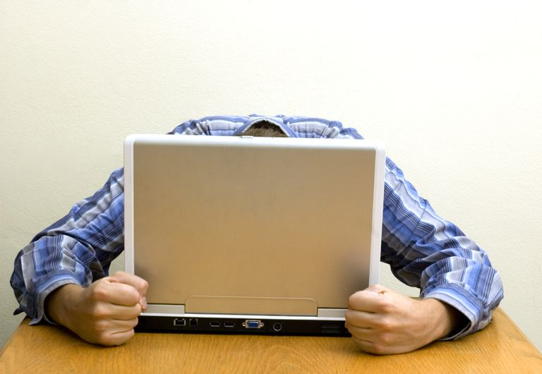 Frustrated man with head behind laptop