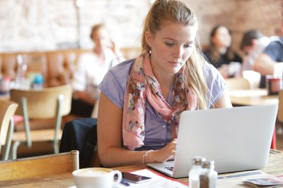 Woman working on laptop in coffee shopp
