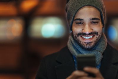 A man looking at his smartphone while smiling