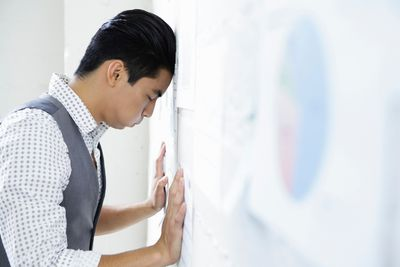 Defeated young man in office with head and hands against wall