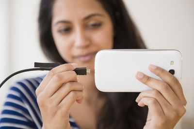 Woman plugging in phone to charge