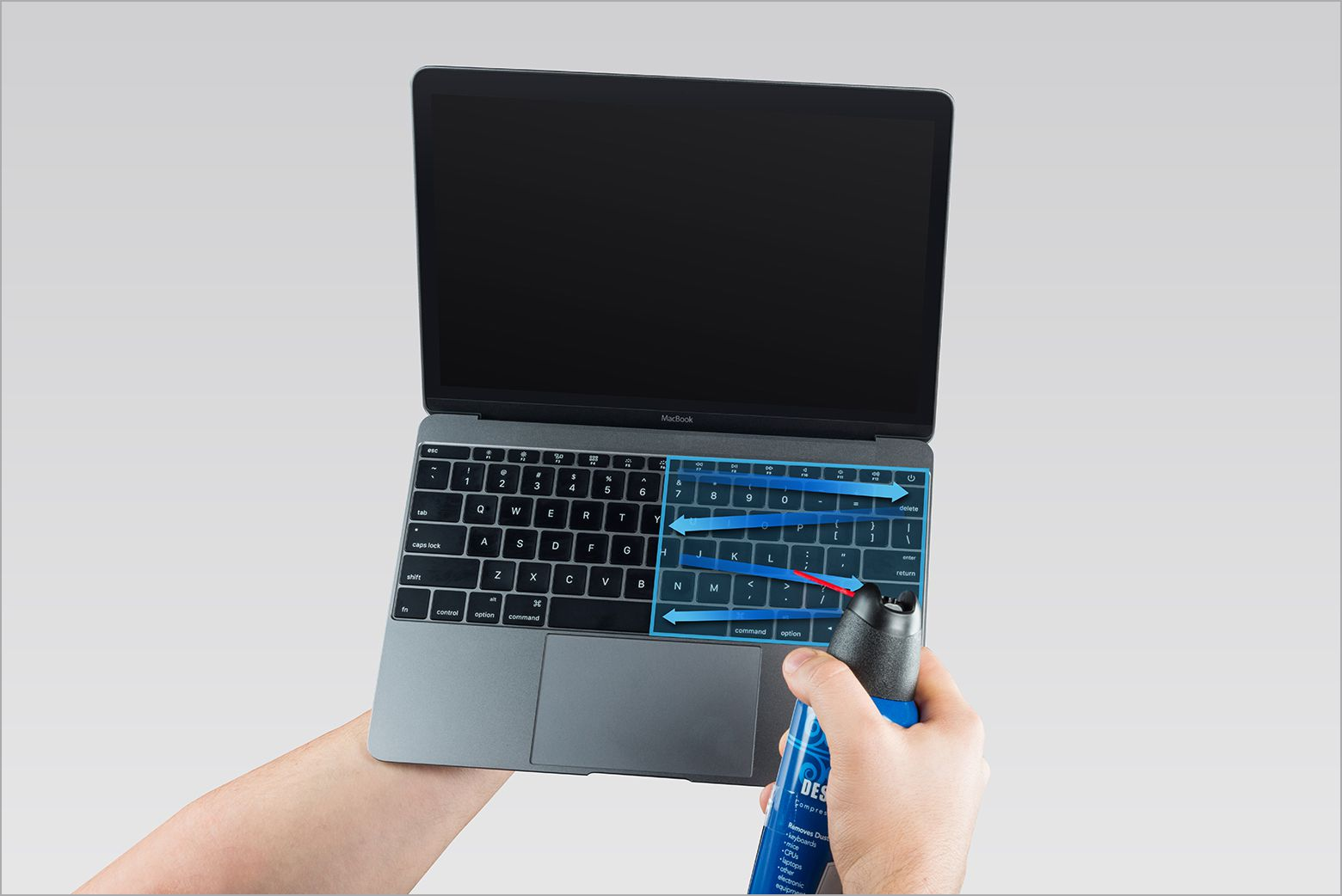 Canned air being used to clean a MacBook keyboard.