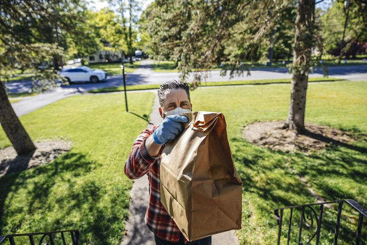 Delivery person holding bag at front door
