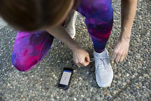 Runner tying shoe and checking heart rate app on cell phone