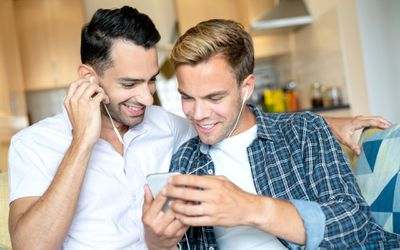 Two men sharing earphones while listening to a podcast on a smartphone.