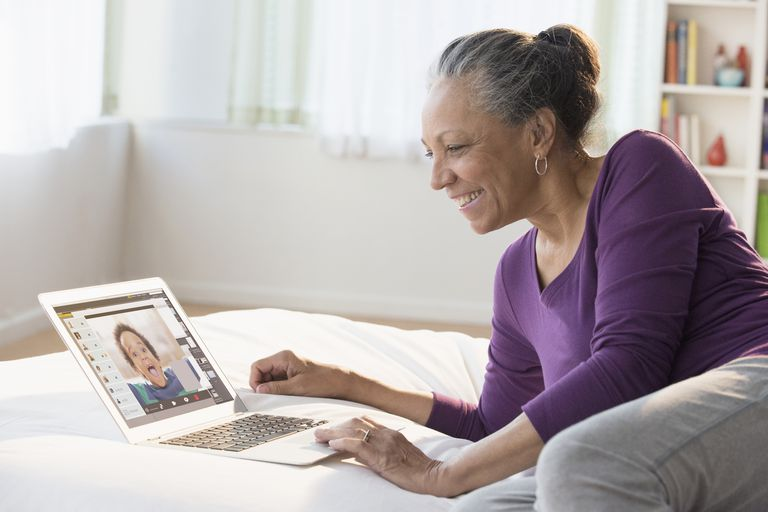 A woman talking to her grandson on Skype through a web browser.