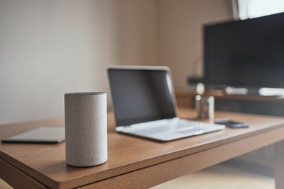 An Amazon smart speaker with a TV in the background