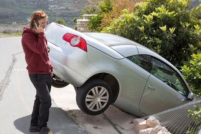 Person on cell phone next to a car that has gone off the road.