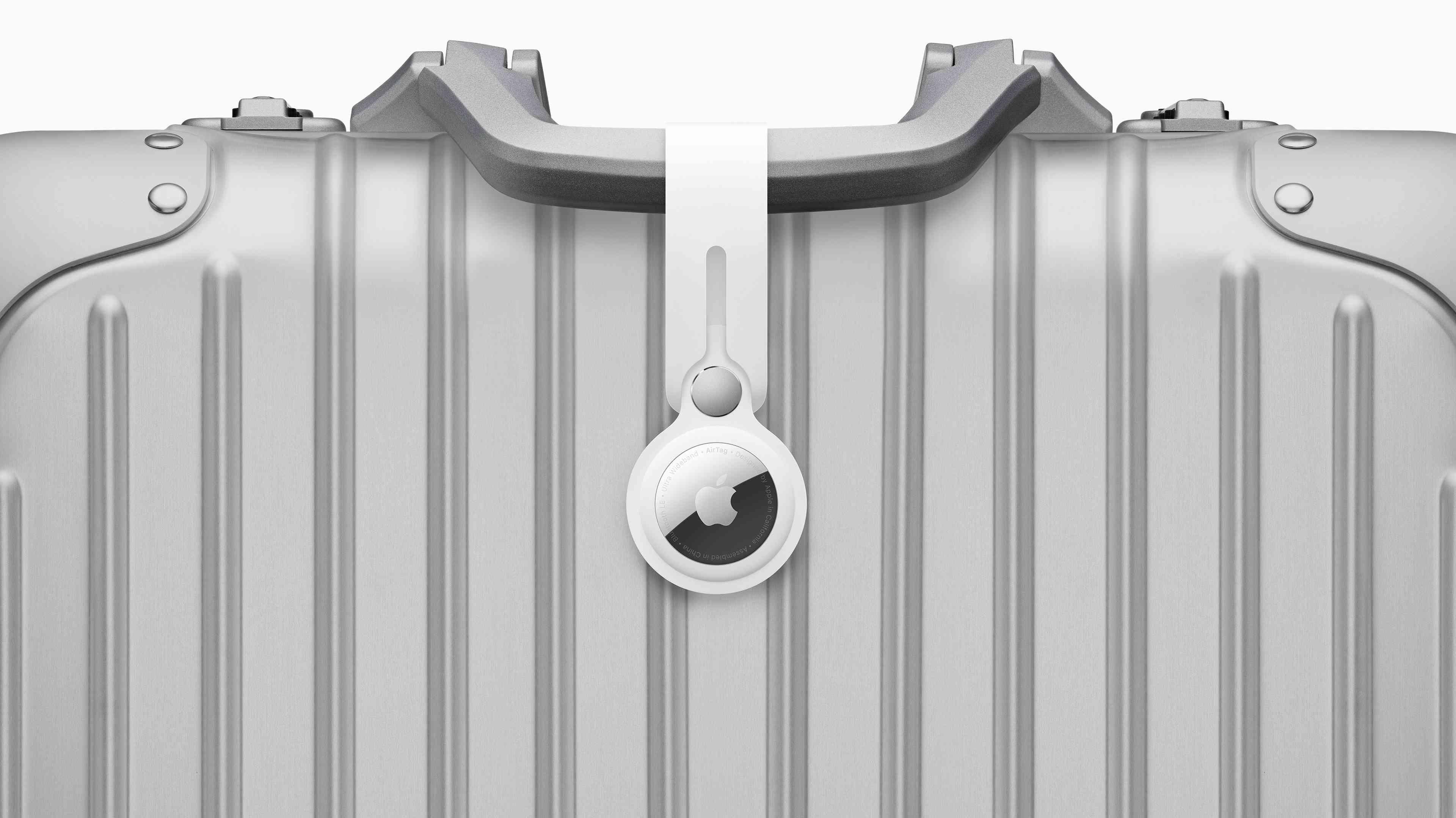 An Apple AirTag on a suitcase handle.