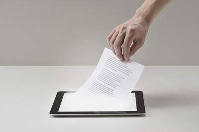 Piece of paper being pulled out of smart tablet