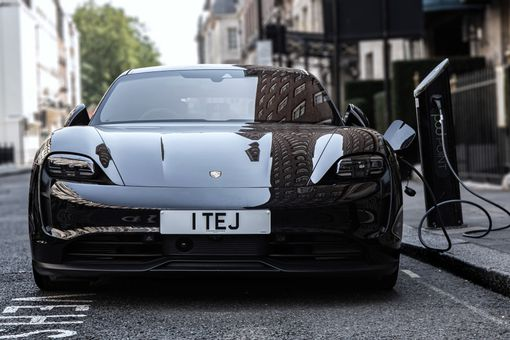 The Proche Taycan all-electric sports car connected to a street-level charger.