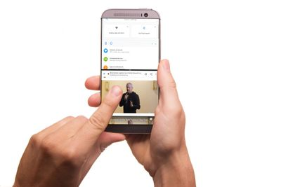 Hands holding an Android phone with split screen mode enabled.