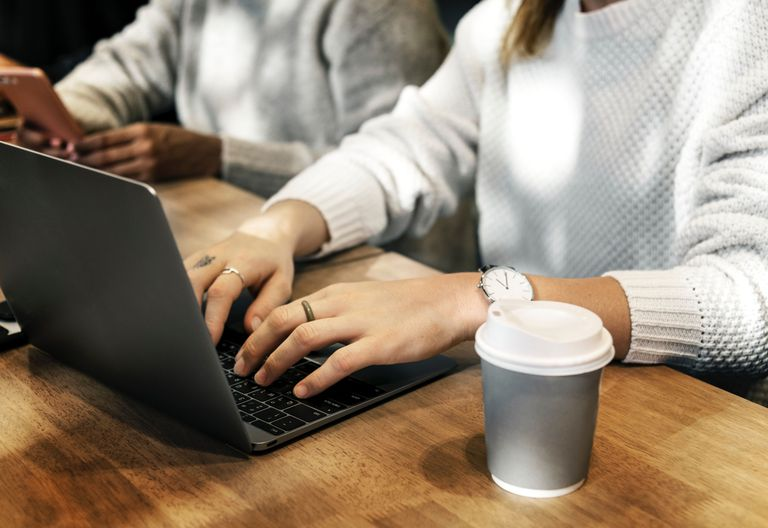 Woman working on laptop with a cup of coffee.