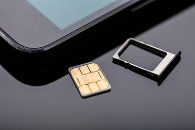 A SIM card next to a smartphone.