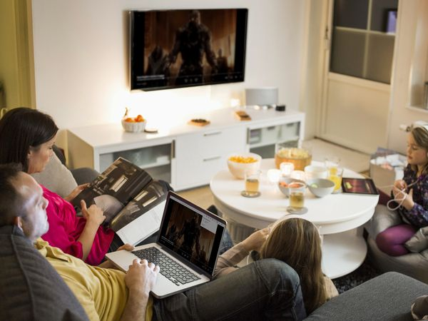 A man sitting on a couch with his wife and daughter while casting HBO Max from his laptop to his TV.