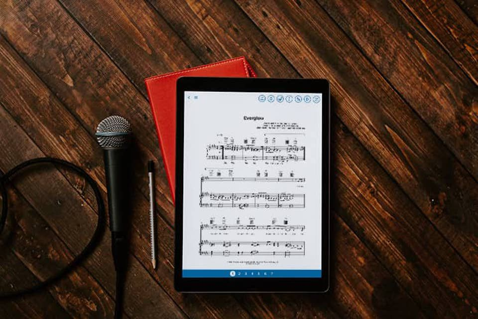 Musicnotes app on an iPad set on a table next to a microphone