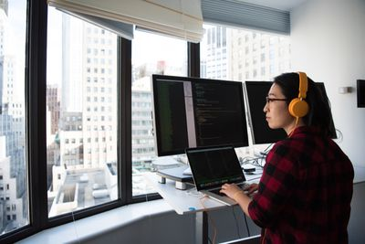 Programmer at work in front of multiple computers