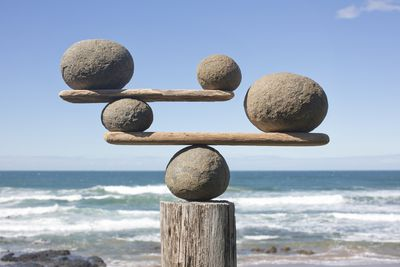 Rocks balancing on driftwood, sea in background