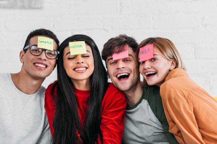 Multicultural friends with funny nickname labels on foreheads