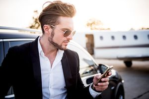 A man wearing sunglasses looking at his iPhone.